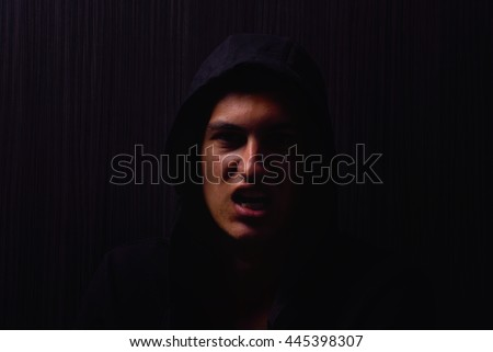 Portrait of teenage boy with serious expression and black hoodie on his head, brown dark hair, direct gaze, yells at the camera. Dark background, lights and shadows - stock photo