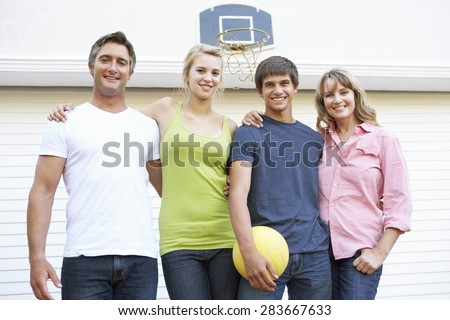 Portrait Of Teenage Family Playing Basketball Outside Garage - stock photo
