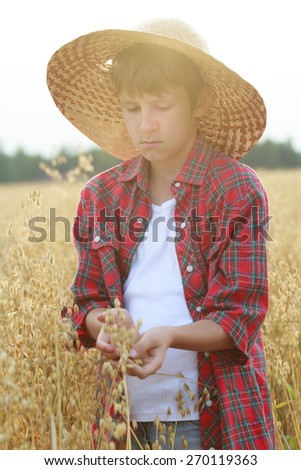 Portrait of teenage farmer boy is holding ripe oat seeds with outer shells in cupped palms with sun flare - stock photo