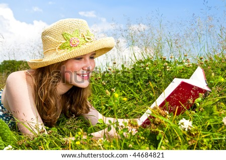 Portrait of teenage girl reading book in summer meadow with straw hat - stock photo