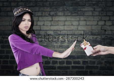 Portrait of teenage girl rejecting to take cigarette and refuse to smoke - stock photo
