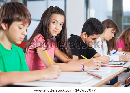 Portrait of teenage girl sitting with classmates writing at desk in classroom - stock photo
