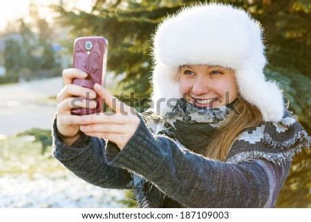 Portrait of teenage girl taking selfie picture with mobile phone outside in winter - stock photo