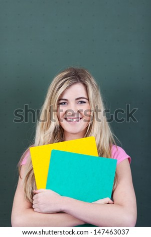 Portrait of teenage girl with files standing against chalkboard in classroom - stock photo