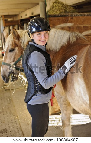 Portrait of teenage girl with horse in stable - stock photo