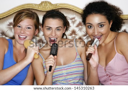 Portrait of teenage girls using brushes as microphones and singing at slumber party - stock photo