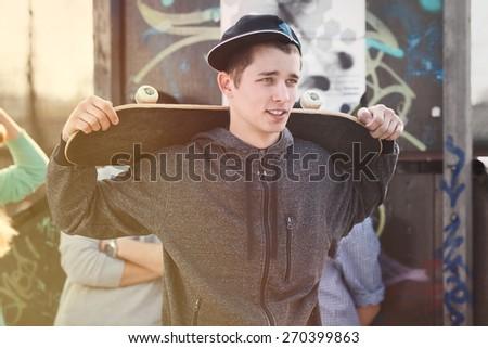 Portrait of teenage skater boy with a skateboard  - stock photo