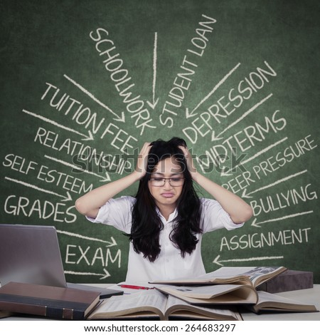 Portrait of teenage student looks frustrated with problems on the blackboard - stock photo