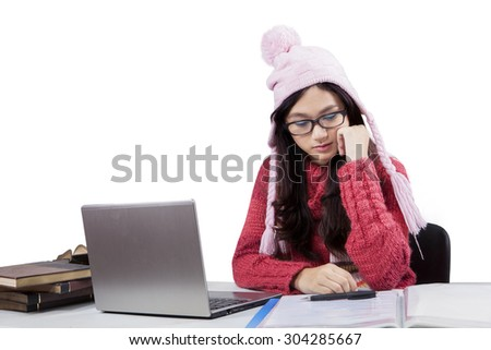 Portrait of teenage student wearing warm clothes and studying with laptop and books, isolated on white - stock photo