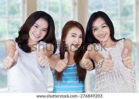 Portrait of teenage students standing in the studio while holding a blank whiteboard, isolated on white - stock photo