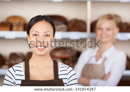 Portrait of teenage waitress smiling with coworker in background at cafe - stock photo