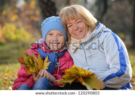 Portrait of teenager girl and senior woman (grand mather) in autumn park - stock photo