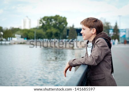 Portrait of teenager on background of river, outdoor - stock photo