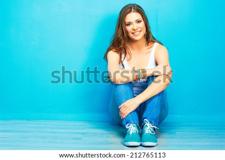 portrait of teenager style female smiling model sitting on floor . pretty woman full body portrait - stock photo