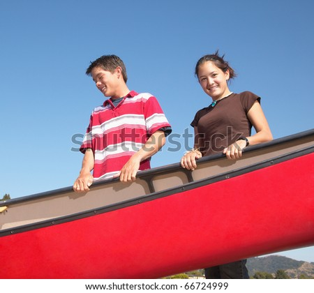 Portrait of teenagers carrying canoe - stock photo