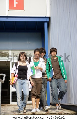 Portrait of teenagers walking with documents - stock photo