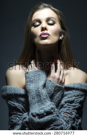 Portrait of tender sensual young woman in grey knitted jacket with bright make up standing with closed eyes on dark wall background, vertical picture - stock photo