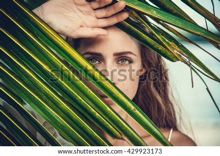 portrait of tender woman looking out of palm leaf - stock photo