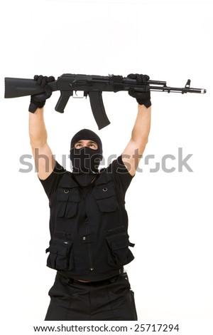 Portrait of terrorist in balaclava holding rifle above himself on white background - stock photo