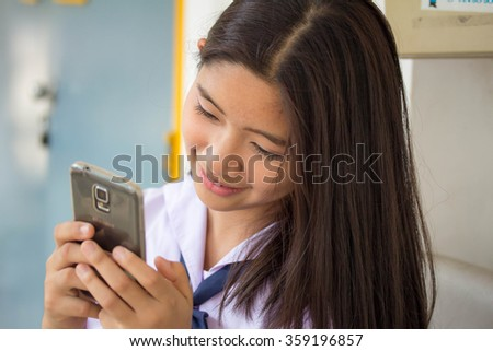 Portrait of thai student teen beautiful girl using her phone and smile. - stock photo