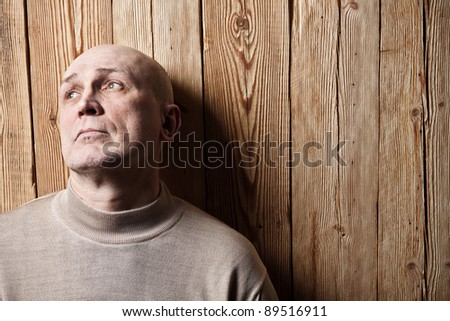 Portrait of the adult person. A wooden background - stock photo