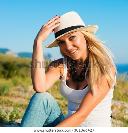 portrait of the attractive, slender, beautiful young Caucasian  blonde girl. Smiling girl enjoys fine warm summer weather high in mountains against the sea - stock photo