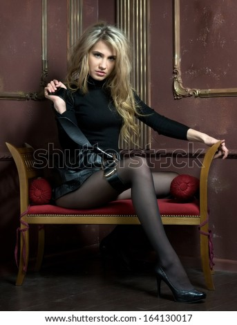 Portrait of the beautiful blonde. She is sitting on the sofa in interior - stock photo