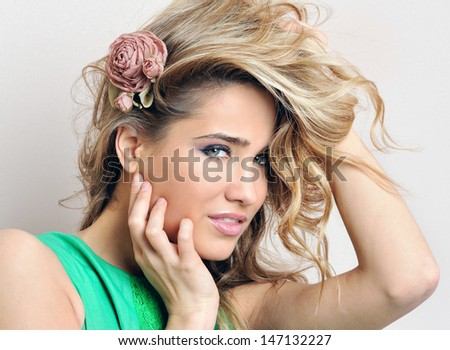 Portrait of the beautiful blonde woman in green dress. - stock photo