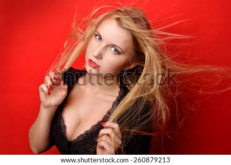 Portrait of the beautiful blonde woman with long flying hair. She dressed in black dress with breast  in studio with red background. - stock photo