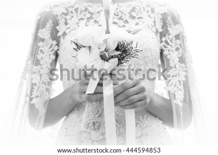 Portrait of the beautiful bride holding the bouquet. black and white - stock photo