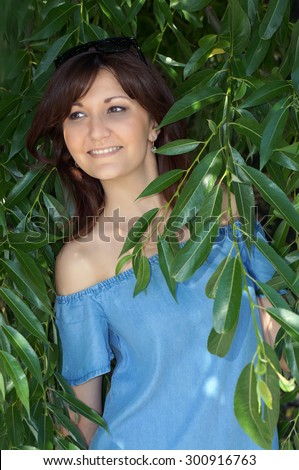 Portrait of the beautiful girl in green leaves of willow - stock photo