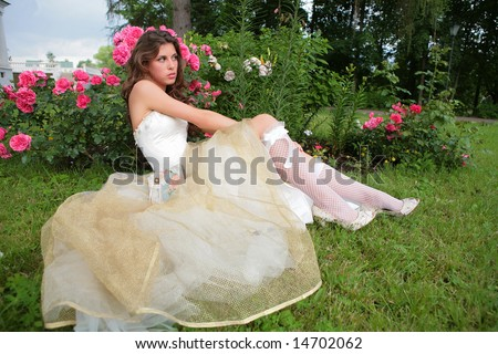 portrait of the beautiful girl in luxurious white-golden gown on background of the rosebush - stock photo
