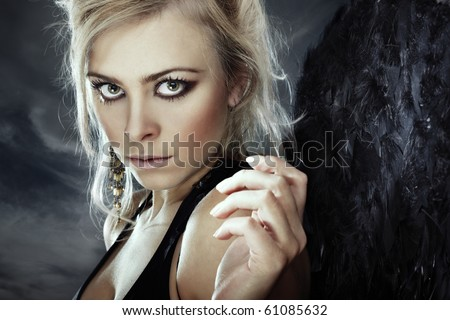 Portrait of the beautiful lady outdoors with black wing as a symbol of fallen angel - stock photo