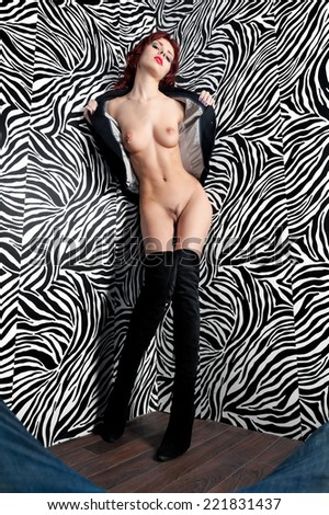 Portrait of the beautiful naked woman in the studio with zebra background - stock photo