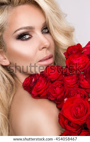 Portrait of the beautiful sexy blonde woman and amazing looks and long hair, perfect skin, she hold bouquet of red roses flowers, dressed in a red  sexy lace lingerie in women's day, Valentine's Day - stock photo