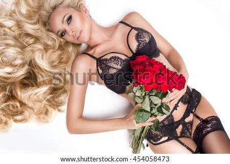 Portrait of the beautiful sexy blonde woman and amazing looks and long hair, perfect skin, she hold bouquet of red roses flowers, dressed in a black  sexy lace lingerie in women's day, Valentine's Day - stock photo