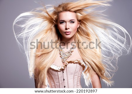 Portrait of the beautiful sexy woman with long blonde hair. Fashion model posing in the studio on a black background with flying hair. - stock photo