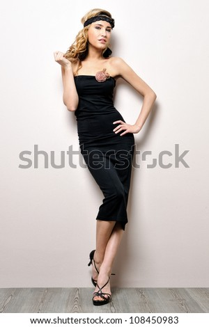 Portrait of the beautiful woman in a black dress. Studio shooting. - stock photo