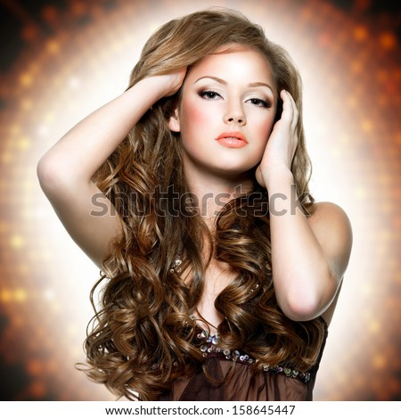 Portrait of  the  beautiful woman with attractive face and  long curly hairs posing at studio - stock photo
