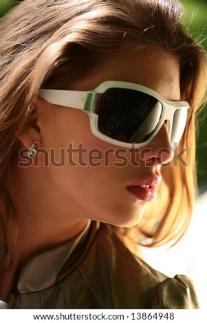 portrait of the beautiful young brunette in big sunglasses, close-up - stock photo