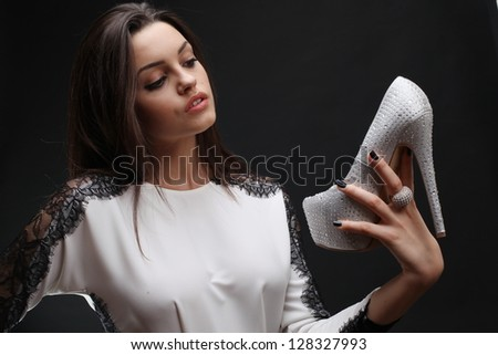 Portrait of the beautiful young girl with a shoe. - stock photo