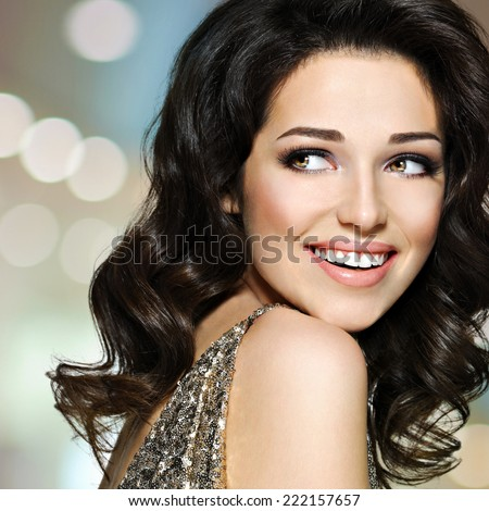 Portrait of the beautiful young happy laughing woman with brown curly hairs looking away. Pretty fashion model with dark eye makeup - stock photo