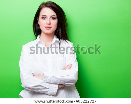 portrait of the beautiful young woman on the green background - stock photo