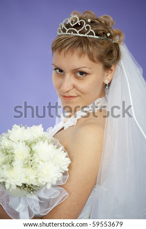 Portrait of the beautiful young woman - the bride on violet background - stock photo