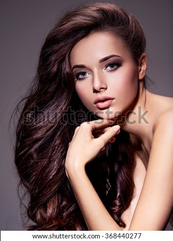 Portrait of the beautiful  young woman with long brown  hair posing at studio over dark background - stock photo