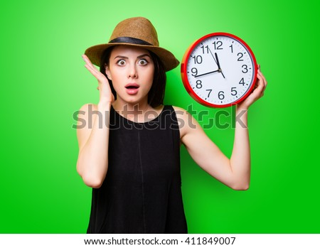 portrait of the beautiful young woman with red clock on the green background - stock photo