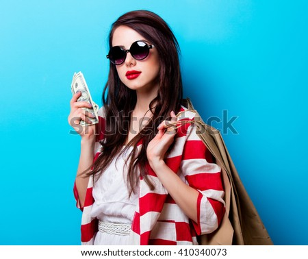 portrait of the beautiful young woman with shopping bags and money on the blue background - stock photo