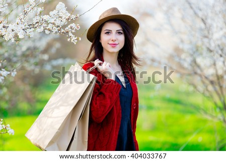 portrait of the beautiful young woman with shopping bags near blooming trees - stock photo