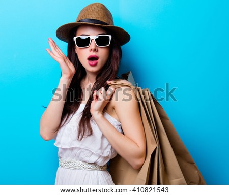 portrait of the beautiful young woman with shopping bags on the blue background - stock photo