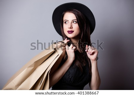 portrait of the beautiful young woman with shopping bags on the grey background - stock photo